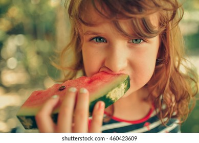 Child eating watermelon in the garden. Kid eat fruit outdoors. Healthy snack for children.