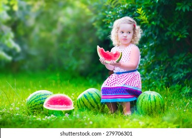 Child eating watermelon in the garden. Kids eat fruit outdoors. Healthy snack for children. Little girl playing in the garden holding a slice of water melon. Kid gardening.