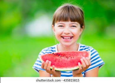 Child eating watermelon in garden. Pre teen girl with teeth braces.