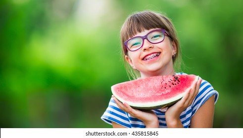 Child eating watermelon in garden. Pre teen girl with gasses and teeth braces.