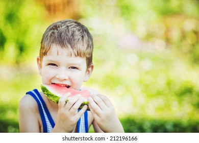 Child eating watermelon in summer park.