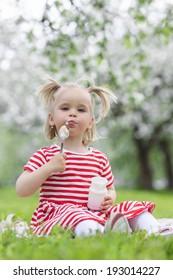 Child eating yogurt in a spring floral park