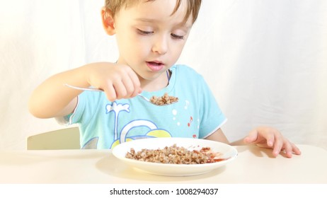The child eats buckwheat porridge with meat, sitting at the table.