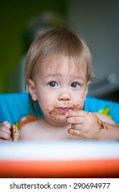 Child eats cake in the highchair. His face and hands smeared with cake