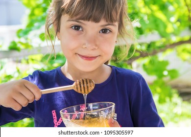 The child eats honey. Selective focus.