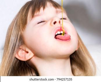 The child eats honey. Selective focus. Close-up