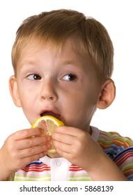 Child eats a sour lemon