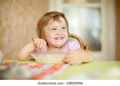 child eats with spoon in home