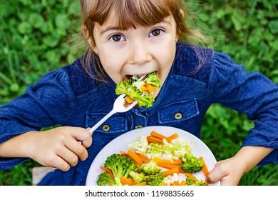 child eats vegetables. Summer photo. Selective focus nature
