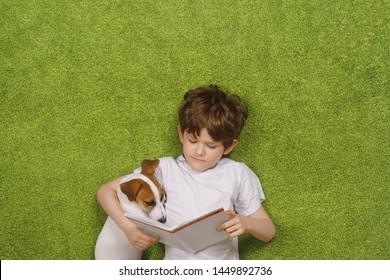 Child embracing friendly dog jack russell was reading the book and lying in green carpet. Education, happy childhood concept.