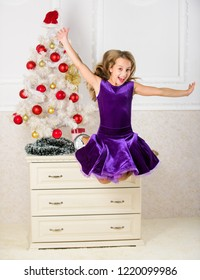 Child emotional cant stop her feelings. Girl in dress jumping. It is christmas. Day we have waited for all year finally here. Girl excited about christmas jump mid air. Celebrate christmas concept.