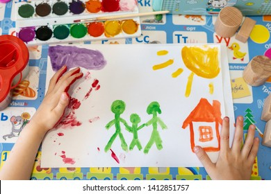 The child is engaged in drawing. Made a handprint and painted house and family with paints. Сreative development of the kid through painting with paints. Colored children's education background.