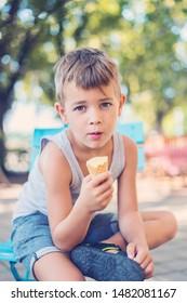 Child enjoying vanilla ice cream in a cone