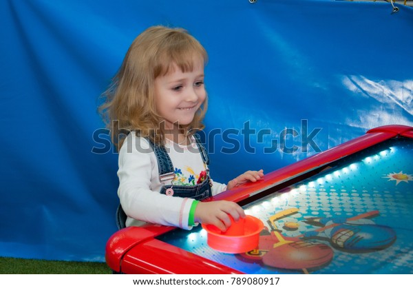The child is entertained in the play center, plays fun in air hockey