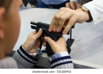 Child examines a gun at the counter in the store