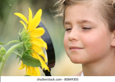 Child examining a sunflower with a magnifying glass