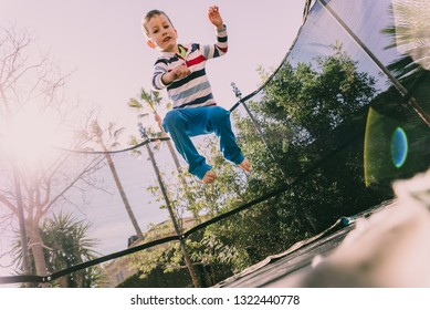 Child exercising in the backyard of his house jumping, casual portrait of his childhood.