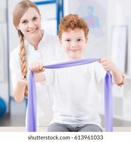 Child exercising with elastic band during rehabilitation with female physiotherapist