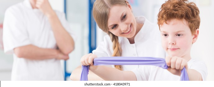 Child exercising with personal physiotherapist at medical clinic