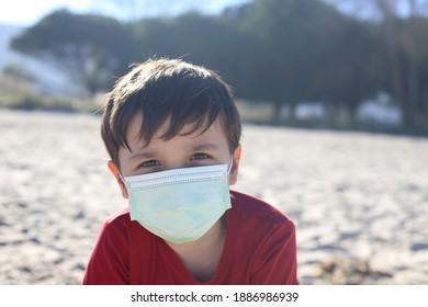Kind mit Gesichtsmaske am Strand