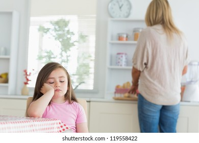 Child falling asleep at kitchen table with mother working on counter