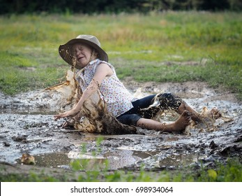 child falls in a puddle. Field. Rural road, mud