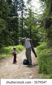 child and father on a trip in the forest