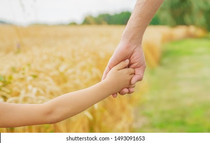 Child and father in a wheat field. Selective focus. nature.