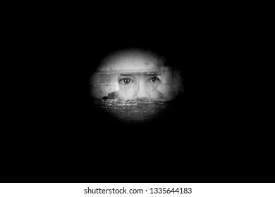 Child fearfully looking through a window