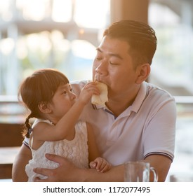 Child feeding bread to daddy at cafeteria. Asian family outdoor lifestyle with natural light.