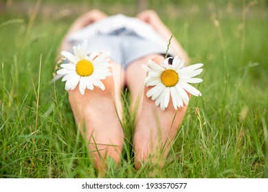 Child feet with daisy flower. Kid having fun at spring nature. Boy lying on green grass outdoors in park. Happy summer feet. Child with daisy lying in sunny meadow and relaxing in summer sunshine.