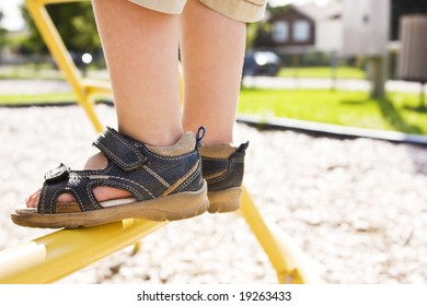 Child feet on a ladder in a playground