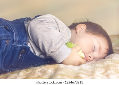 The child fell asleep on the couch with an apple in his hand