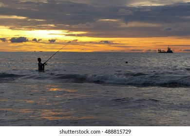 a child fishes at sunset