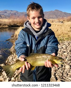 Child fishing in the winter in a coat and sweatshirt, holding a large fish (brown trout) on a mountain river