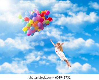 Child flies on the balloons. Blue sky, clouds. A little girl in a white dress