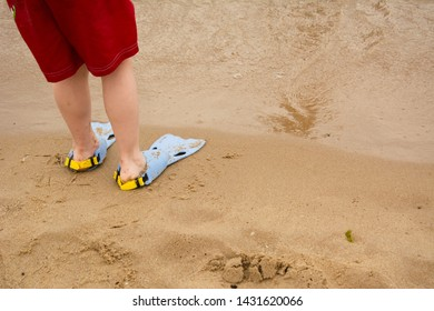 A child in flippers on the sand. Beach, blue flippers, red boxers.