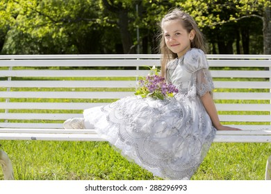 Child with flowers rests on a bench