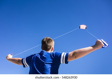 Child flying a kite in the clear blue sky.
