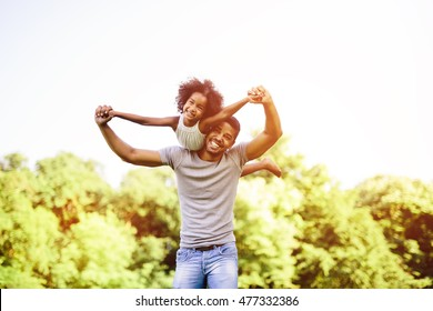 Child flying on father shoulders while held piggyback