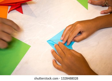 Child folding blue color paper
