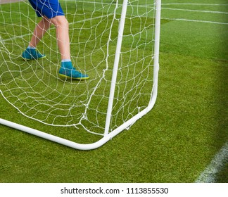 Child football concept: goalkeeper in goal in summer