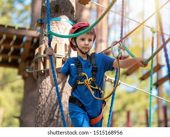Child in forest adventure park. Kid in red helmet and blue t shirt climbs on high rope trail. Agility skills and climbing outdoor amusement center for children. Young boy plays outdoors.
