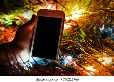 The child found a gift in the form of a white smartphone under the tree for the new year. Christmas present in the light of the bright colored lights from the glowing garland