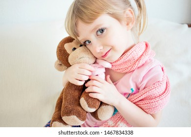 The child is freezing in a scarf. Cute baby soft hug a toy. Baby with toy monkey. Hugs. Love and tenderness. Beautiful little girl, long eyelashes, white hair, short tails.