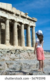 Child in front of Facade of ancient temple Parthenon in Acropolis Athens Greece on the blue sky background