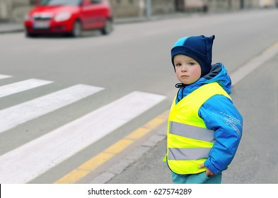 Child in front of pedestrian crossing. Little boy finds out if he can cross the zebra crossing. He wears reflective vest because of safety. Car in the background. Child concept. Traffic concept.