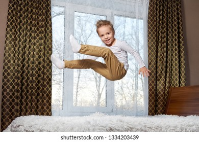 child fun home. Beautiful blond child 6 years old fooling around morning to room. Kid smiling jumping to bedroom on bed.