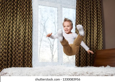 child fun home. Cheerful boy in motion jumping laughing on bed. Little kid of 6 years old happily plays morning in room.