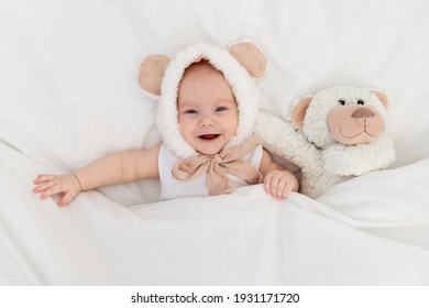 a child in a funny hat with ears with a teddy bear under the blanket. Textiles and bed linen for children. A newborn baby has woken up or is going to bed